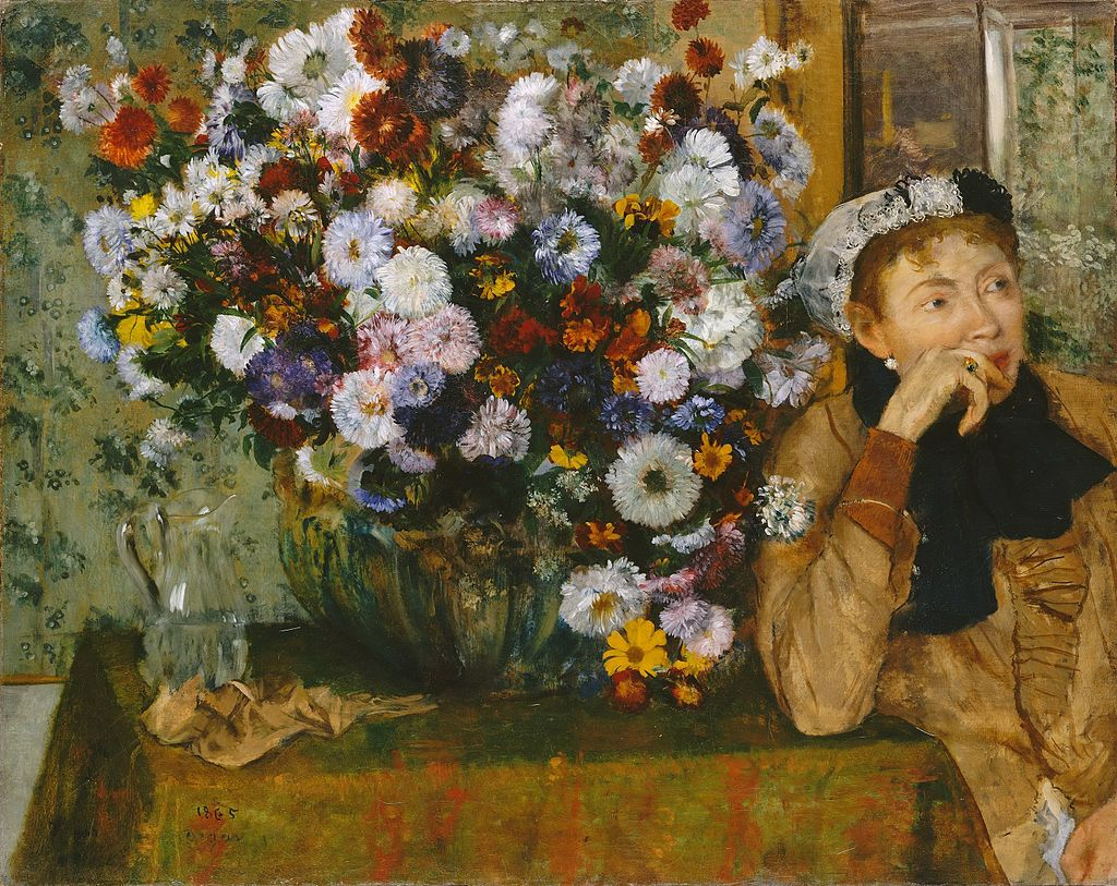 A woman, her head propped up by her hand, looks absent mindedly out of the frame beyond the viewer. She is sitting by a small table on which is placed a huge display of flowers in a vase. The flowers are complemented by floral wall paper in the background.