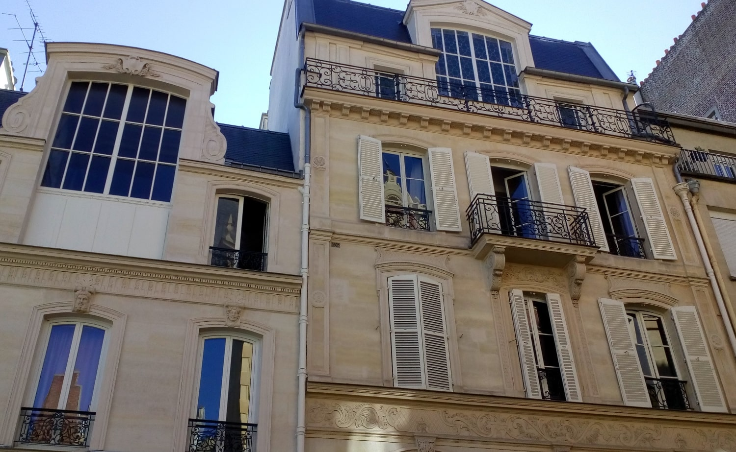 Photograph of 23 Rue Ballu Paris 75009. We see an apartment facade with large artist studio type windows on the upper floors of the building. Edgar Degas lived and worked here from 1890 – 1897.